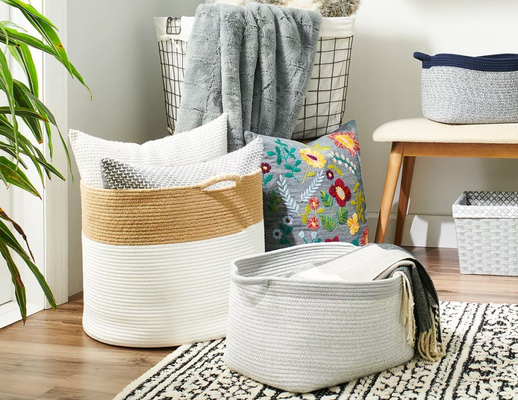 two rope laundry bins on floor with pillows and blankets inside