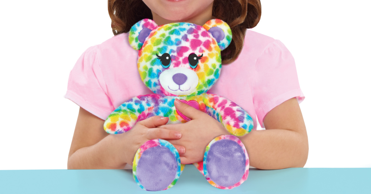 Rainbow colored bear plush on blue counter