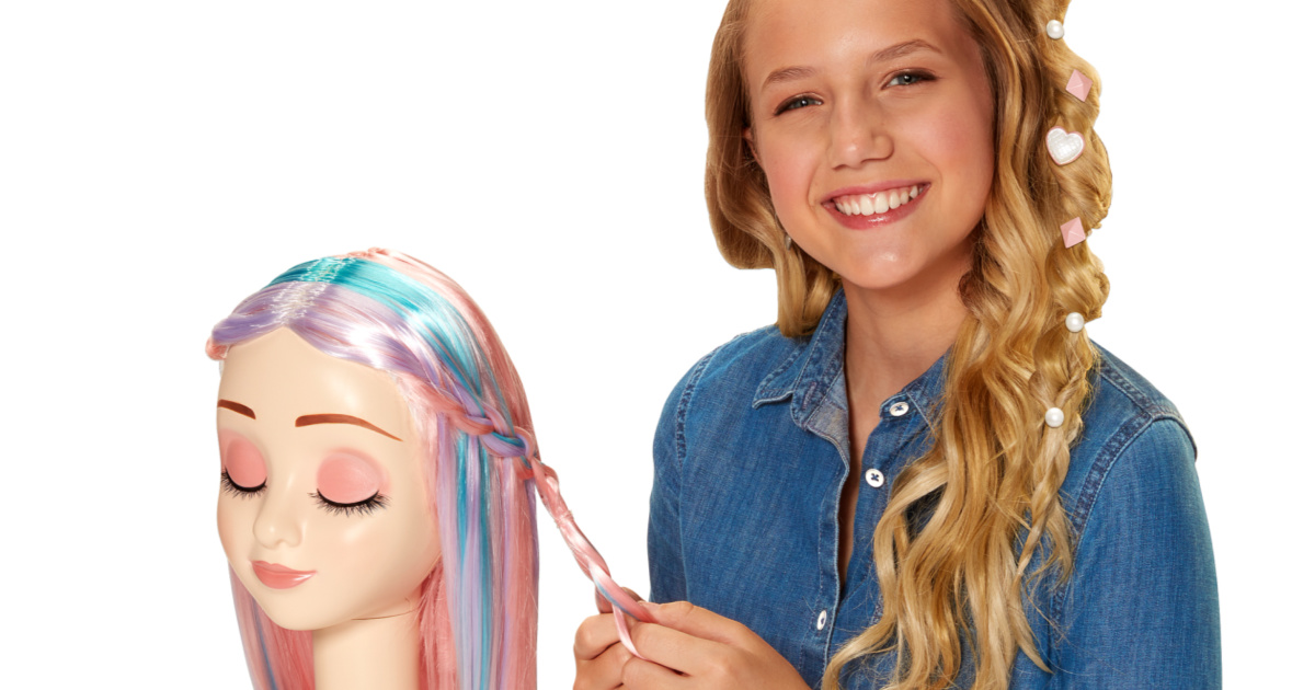 girl braiding a multicolored wig on a doll form