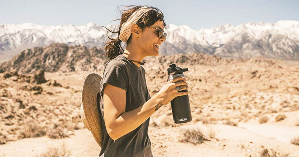 woman standing in desert holding a camelbak water bottle