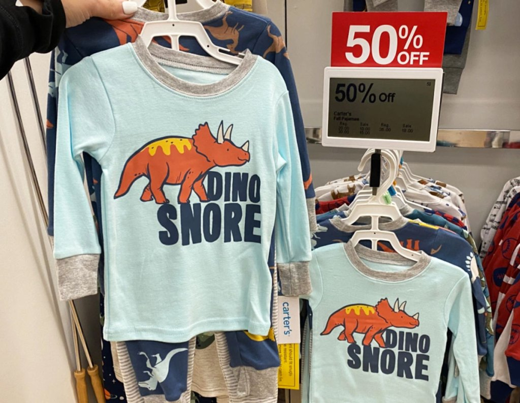 person holding up dinosaur printed pajama set next to 50% off sale sign