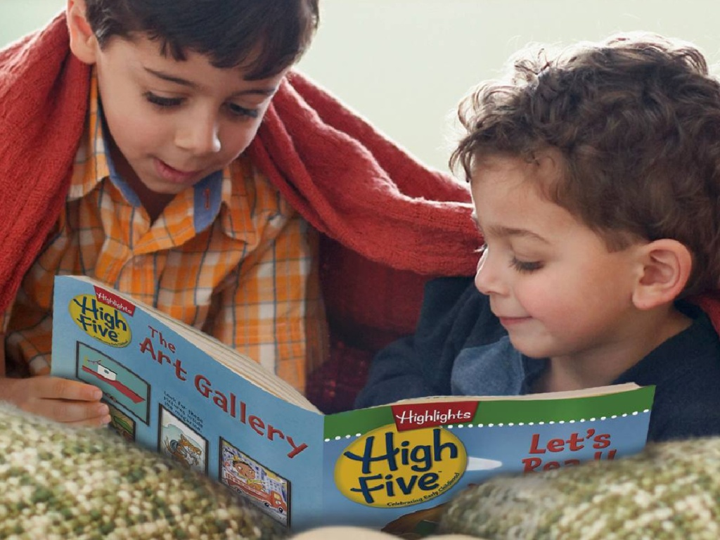 two little boys laying under a blanket reading highlights high five kids magazine