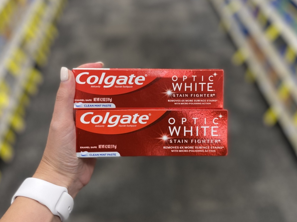woman's hand holding 2 boxes of colgate toothpaste at cvs
