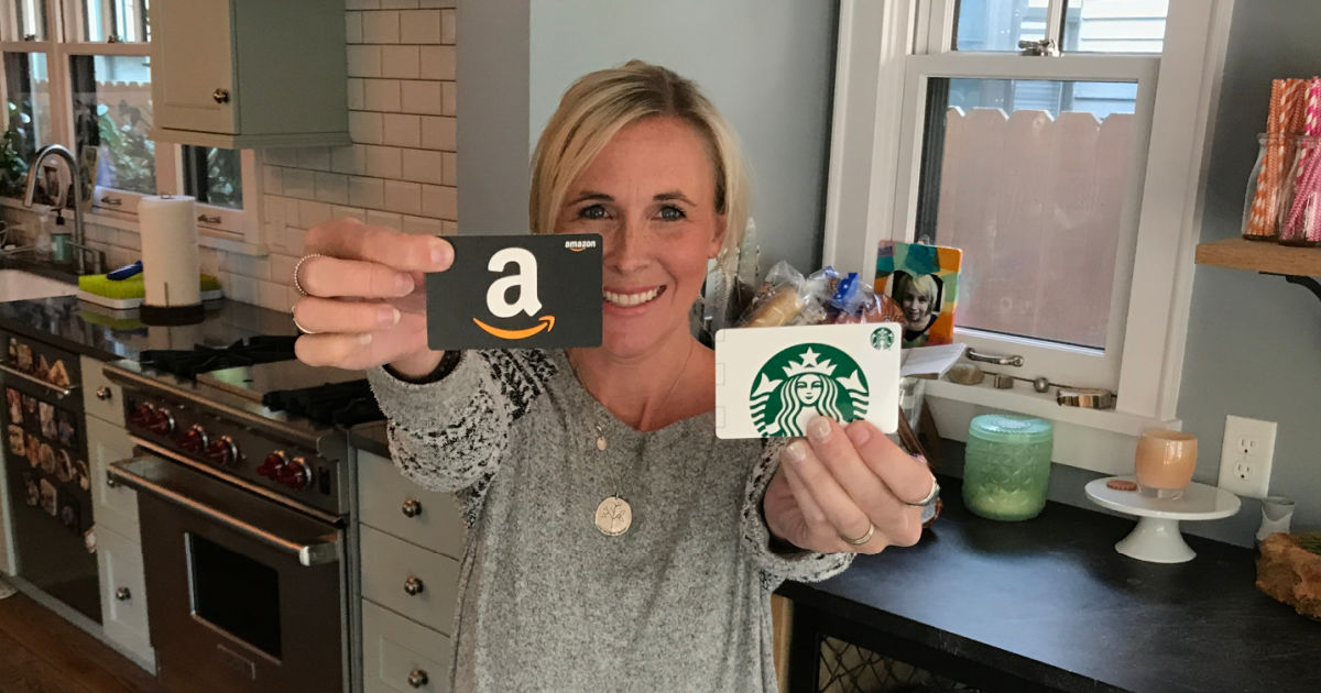 woman holding starbucks and amazon gift cards in kitchen