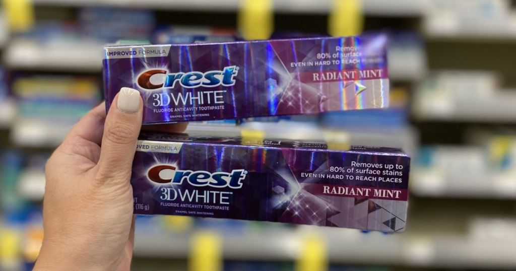 hand holding 2 Crest 3D White Toothpastes