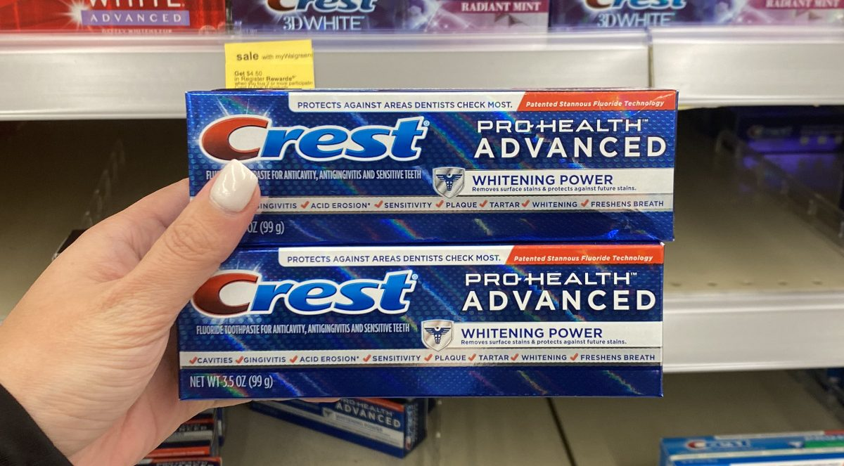 woman's hand holding two toothpastes in store