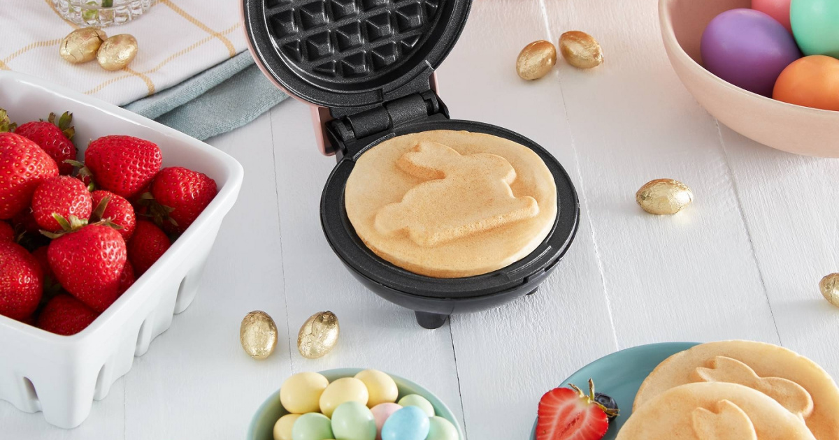 mini waffle maker with bunny waffle on table between bowl of dyed eggs and basket of strawberries