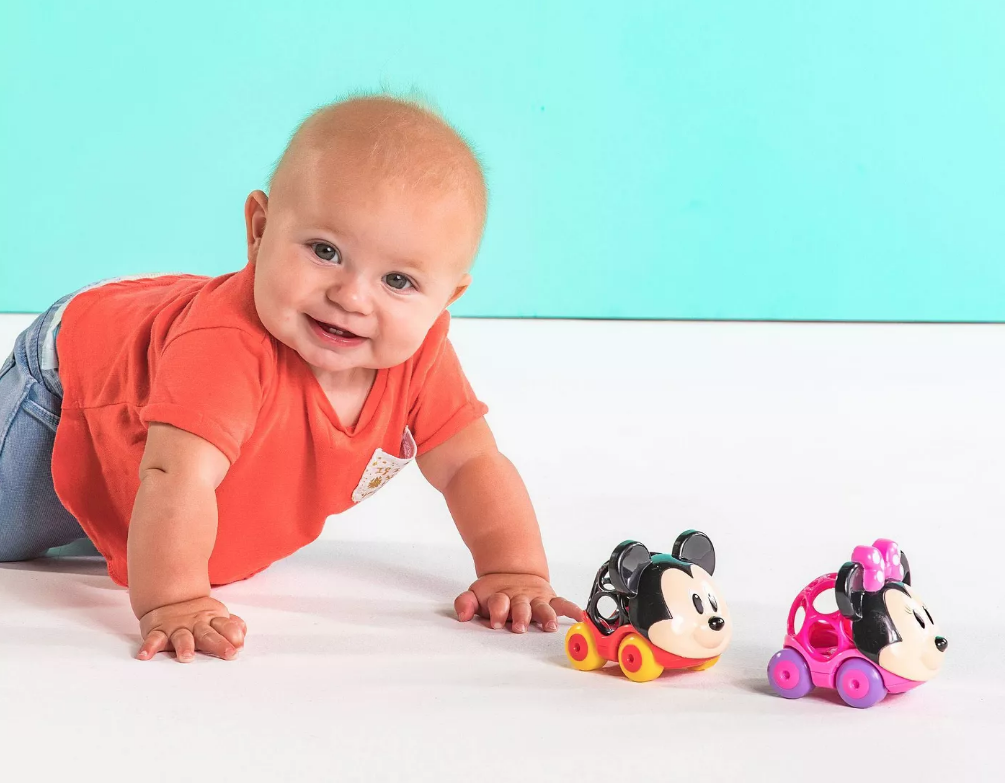 Baby crawling after Disney Mickey and Minnie oball Gripper Cars