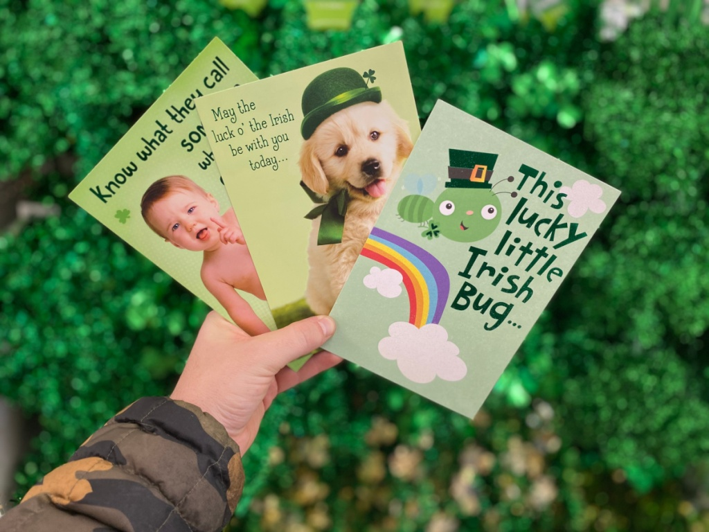 man's hand holding St. Patrick's Day cards in front of green garlands in store