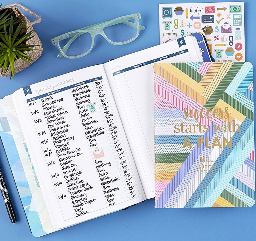 rainbow journal with glasses and stickers near it