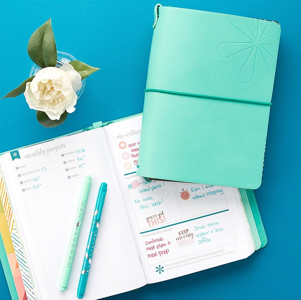 two planners with pens on one of them