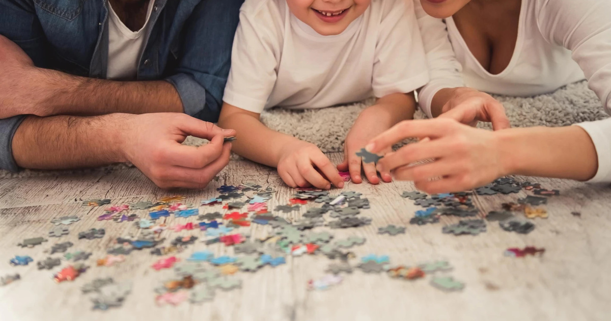 Family putting together a puzzle on the floor