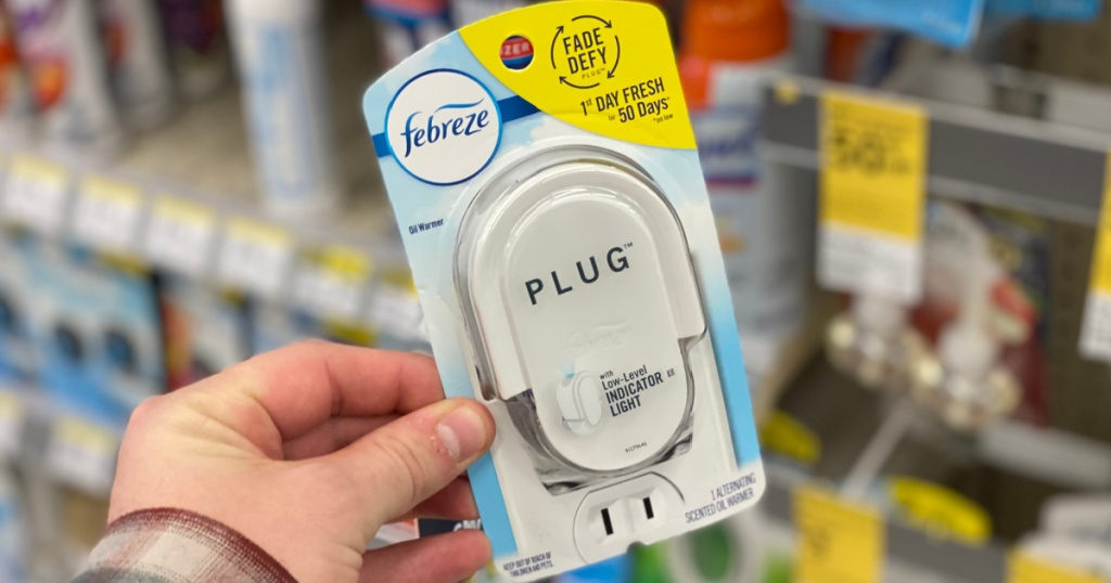 hand holding a febreze plug-in warmer at walgreens