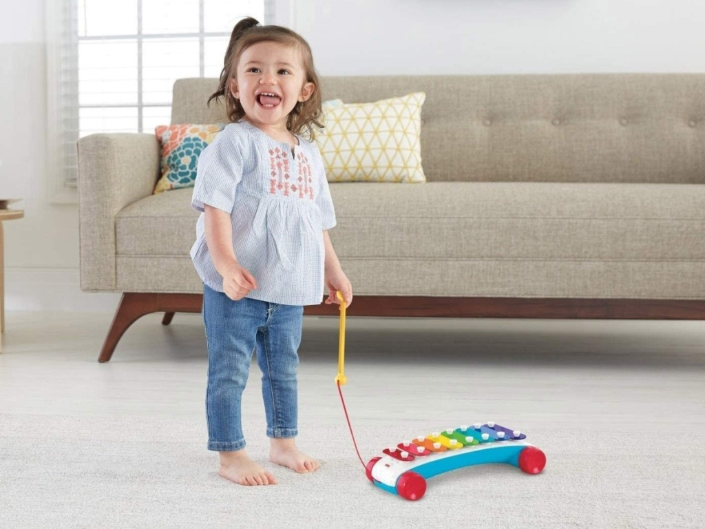 little girl playing with a Fisher-Price Classic Xylophone