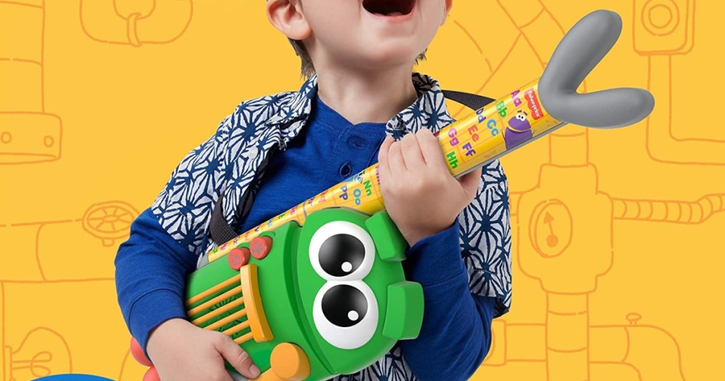 Young boy holding an interactive toy guitar