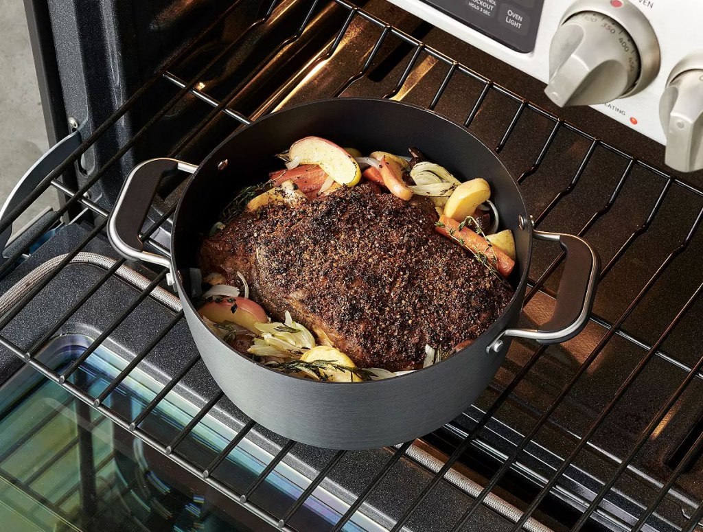 black stockpot on oven shelf with a roast inside of it