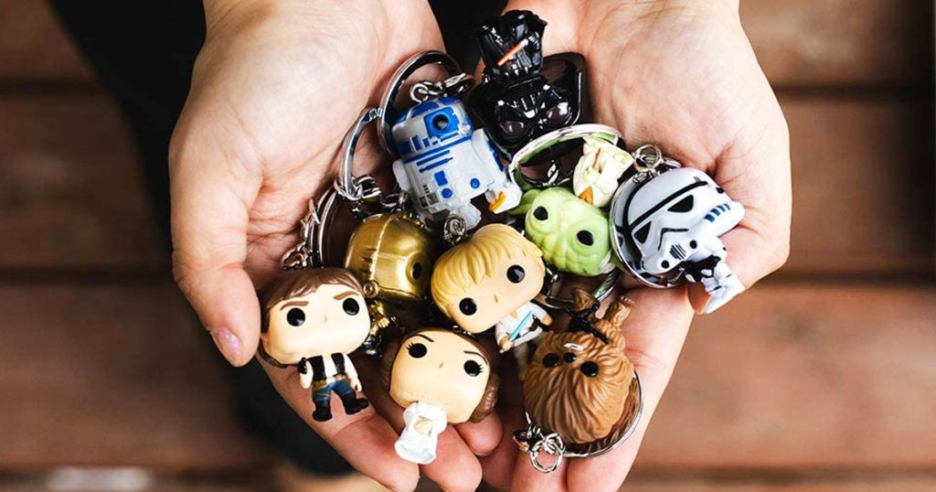 hands holding a collection os star wars keychains