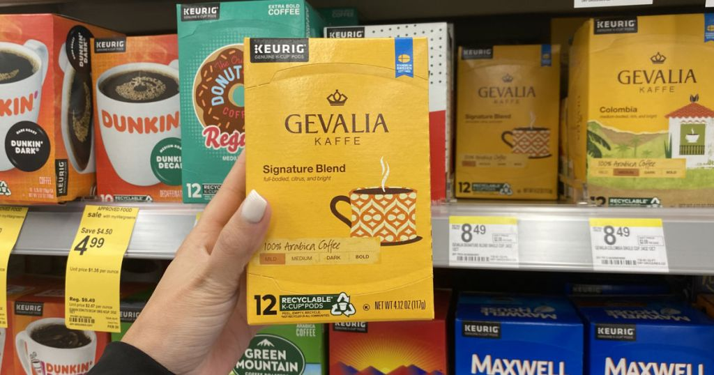 hand holding yellow box of coffee pods