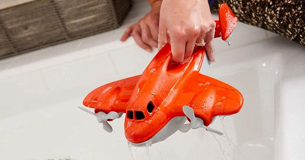 holding red plane toy near bath tub water