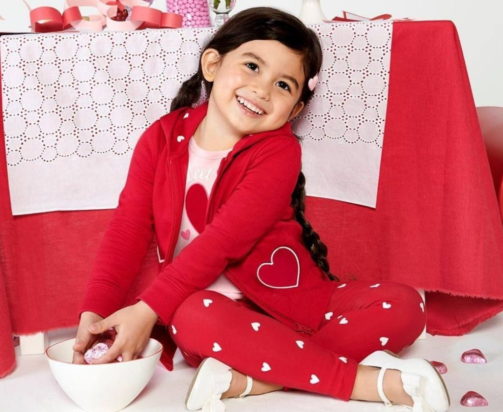 Little girl dressed in Valentine Theme clothing with bowl of heart shaped cadies