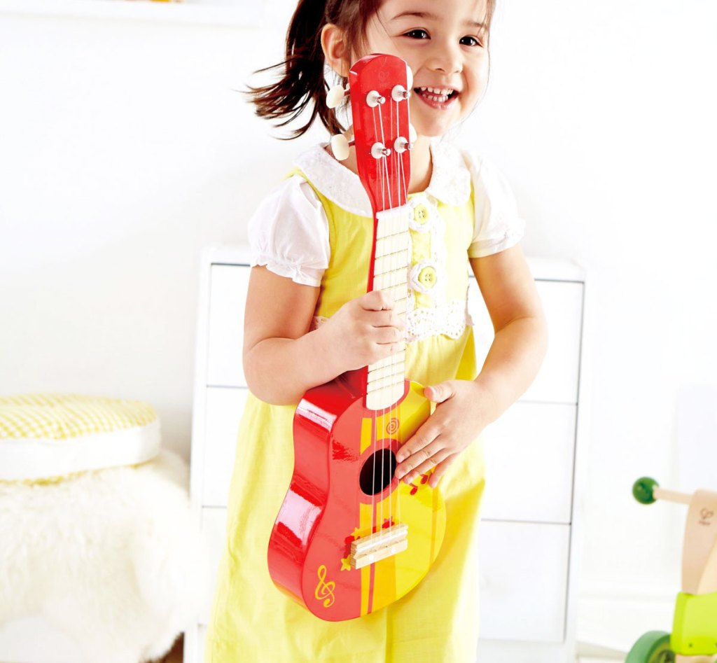 girl in yellow dress holding a red ukulele