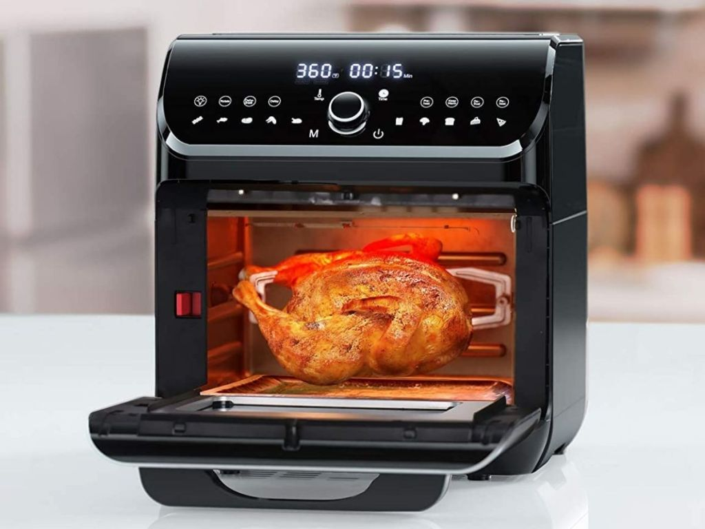 black air fryer oven opened showing chicken on rotisserie