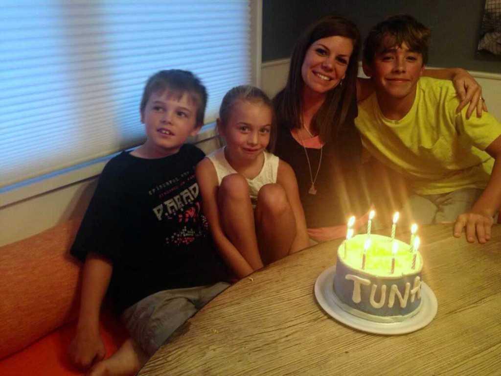 woman with three kids and birthday cake