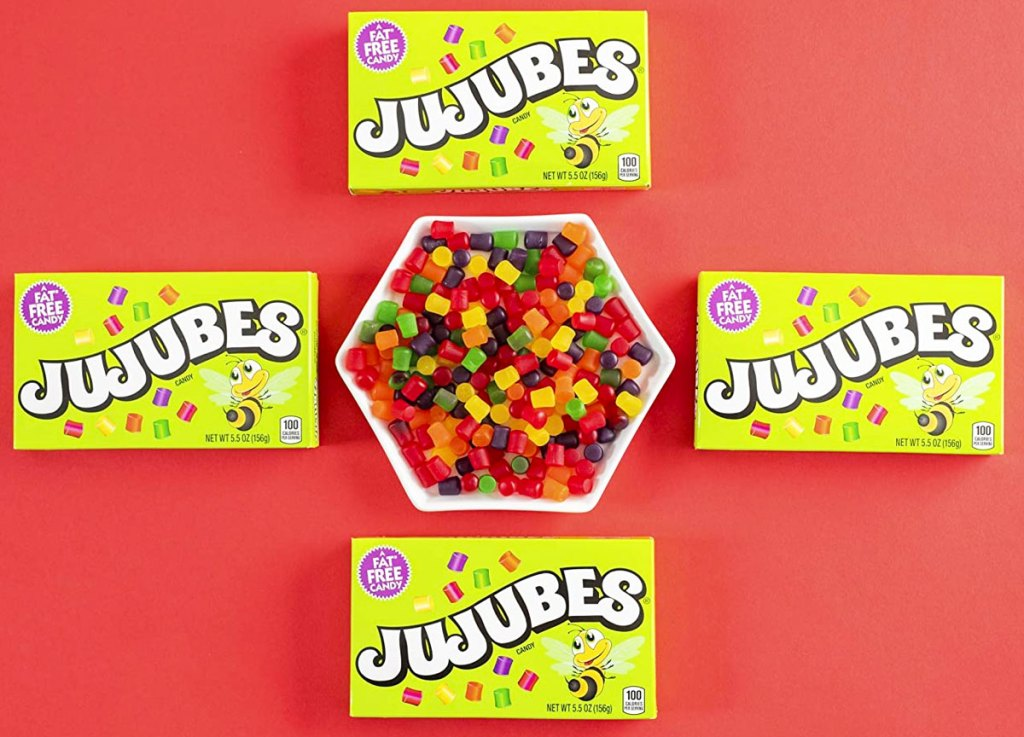 four boxes of jujubes candy around bowl of candy