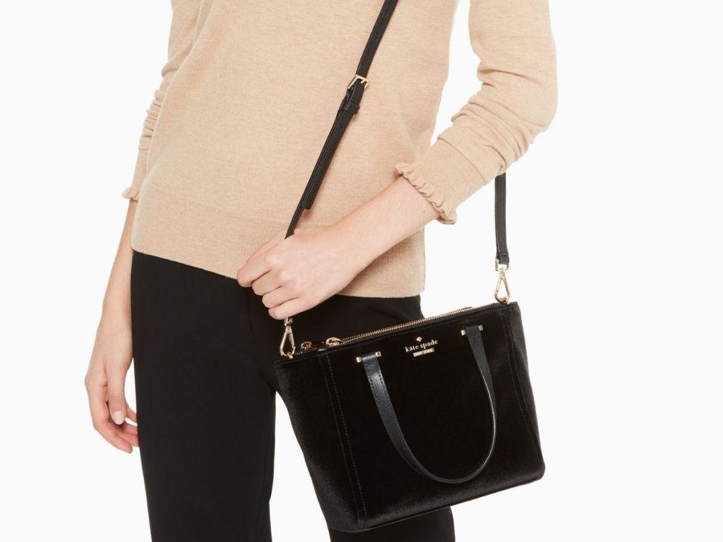 woman holding black Kate Spade bag
