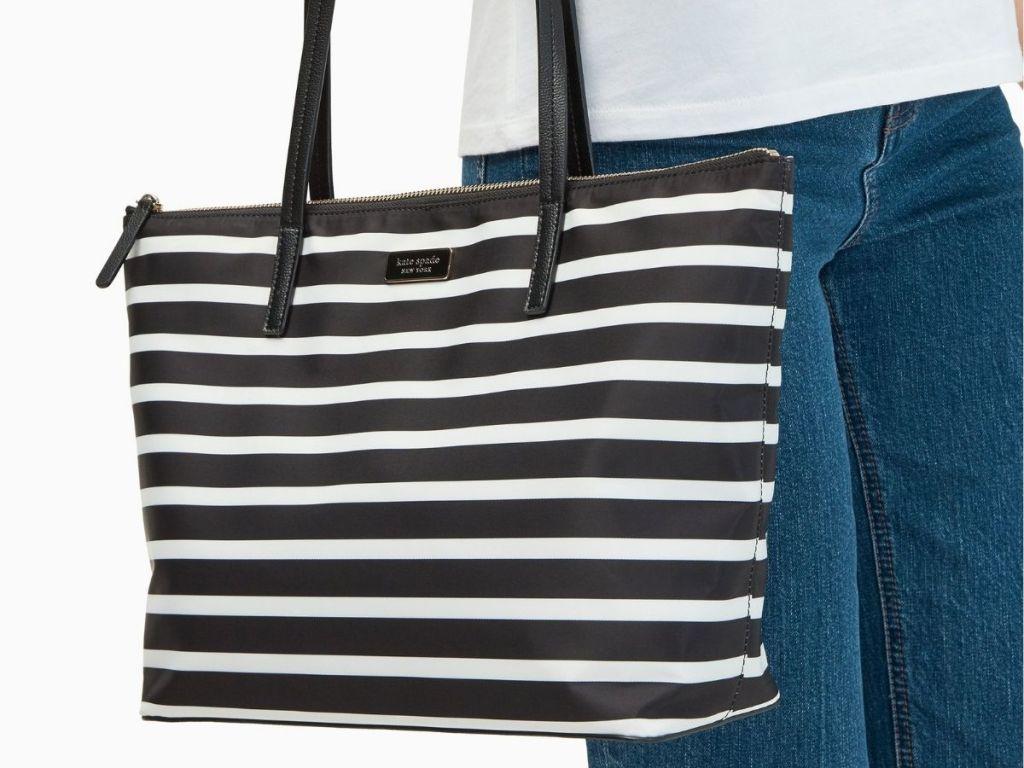 woman carrying Kate Spade striped bag