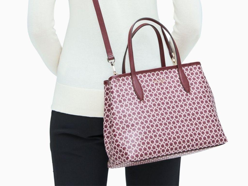 woman carrying burgundy tote bag