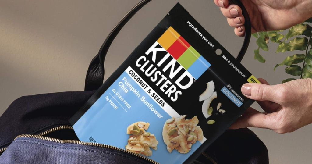 hand holding a bag of kind coconut clusters