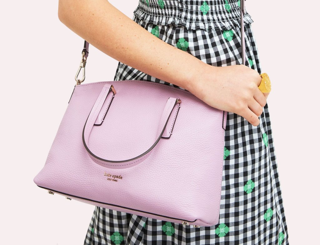 woman in black and white gingham dress with lilac colored satchel