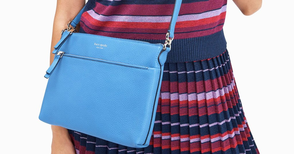 woman in striped dress with blue crossbody bag