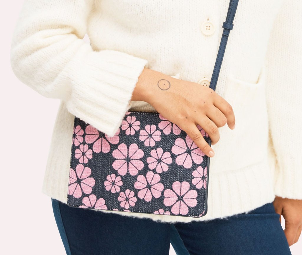 woman in white sweater with blue and pink floral print crossbody