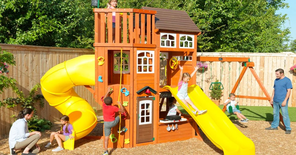 kids playing on wooden backyard playset with swings and multiple yellow slides