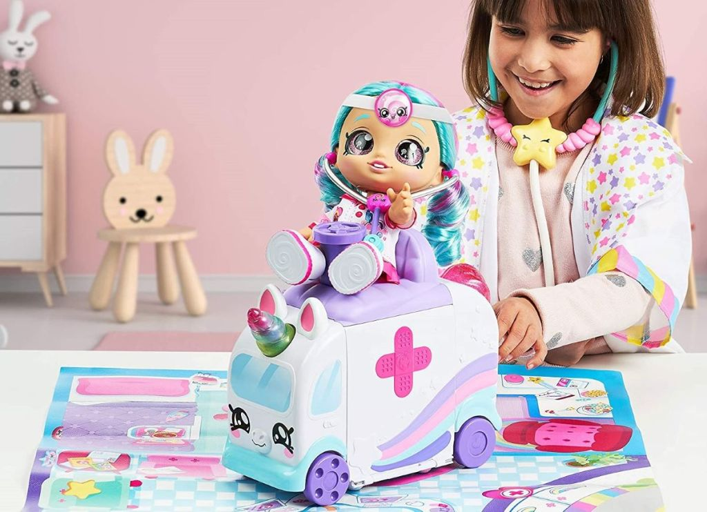 girl playing with a doll ambulance
