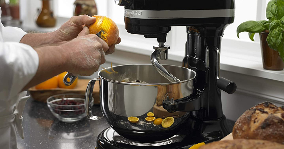 mans hands zesting an orange into the bowl of a black kitchenaid stand mixer on a granite countertop