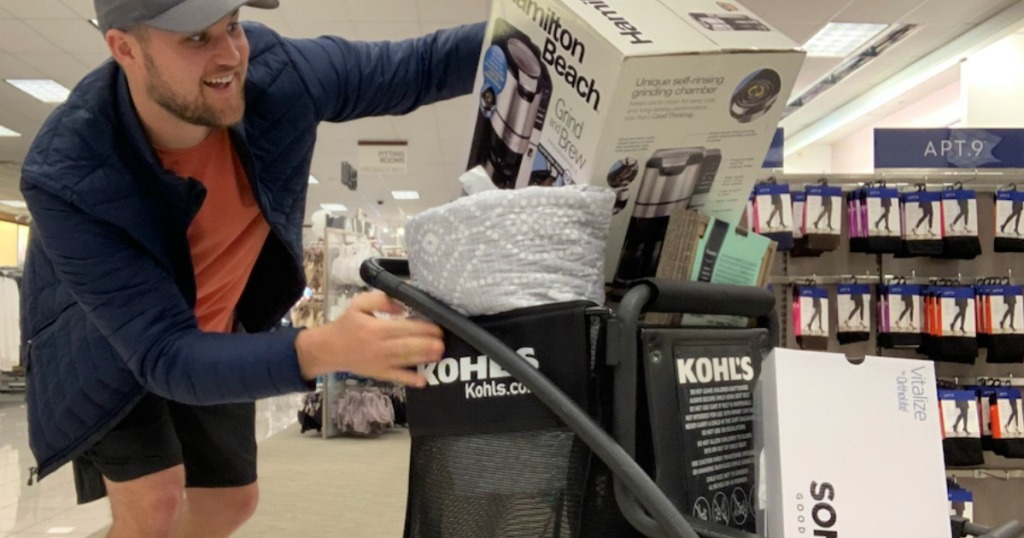 man pushing a kohl's shopping cart filled with merchandise