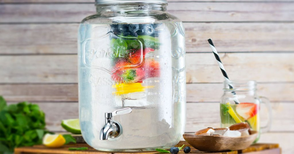 glass beverage dispenser with fruit infuser inside on a wood table