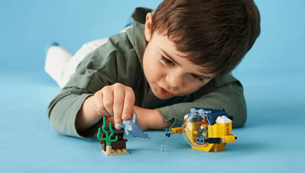 boy playing with LEGO set