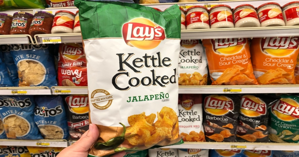 a hand holding a bag of Lay's Kettle cooked chips in store, in front of all bagged stocked chips in store