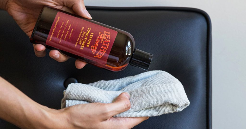 person pour leather conditioner on a towel