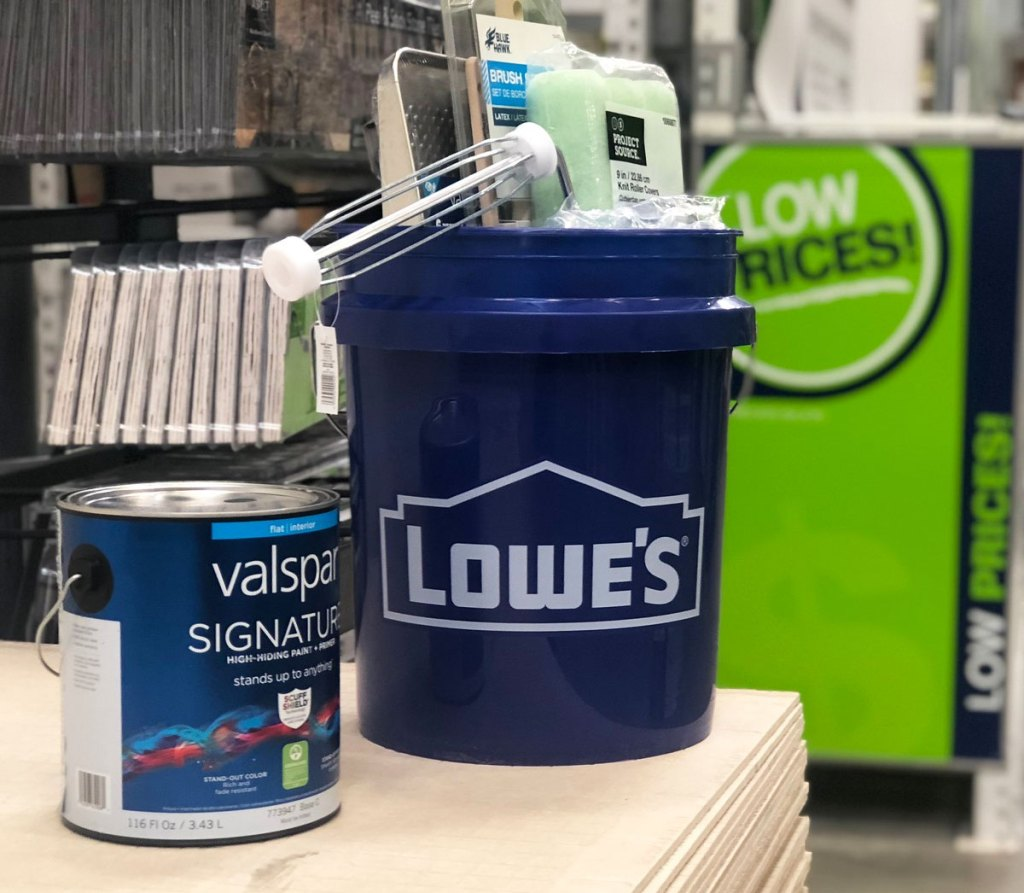 can of paint and blue lowe's bucket full of painting supplies