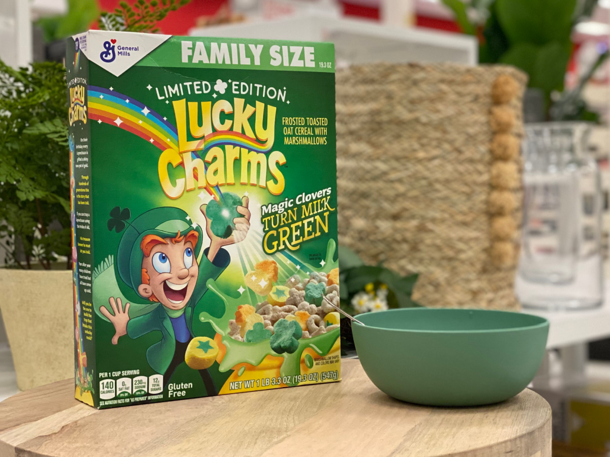 Box of Lucky Charms cereal on a table with a green bowl
