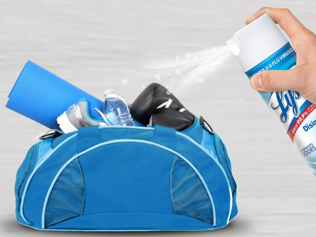 hand holding a lysol can spraying a stinky gym bag