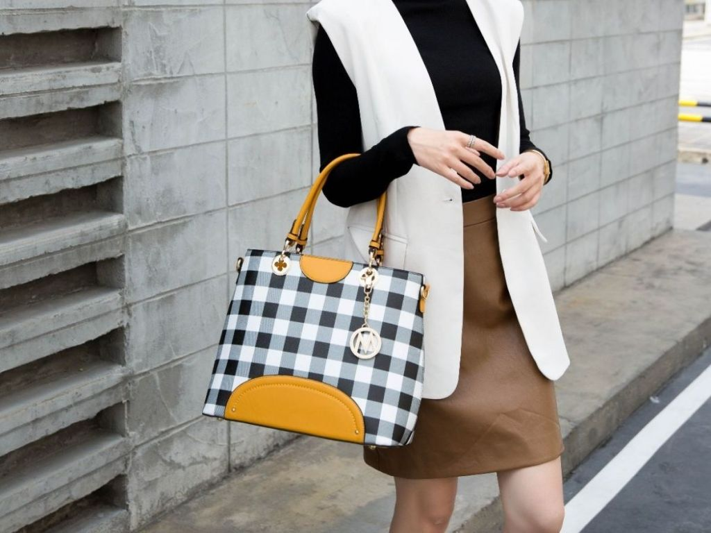 woman holding black and white check tote bag
