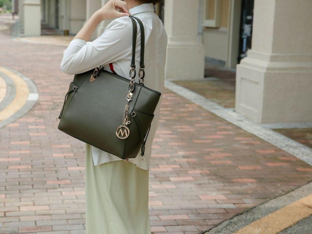 woman holding dark green tote bag