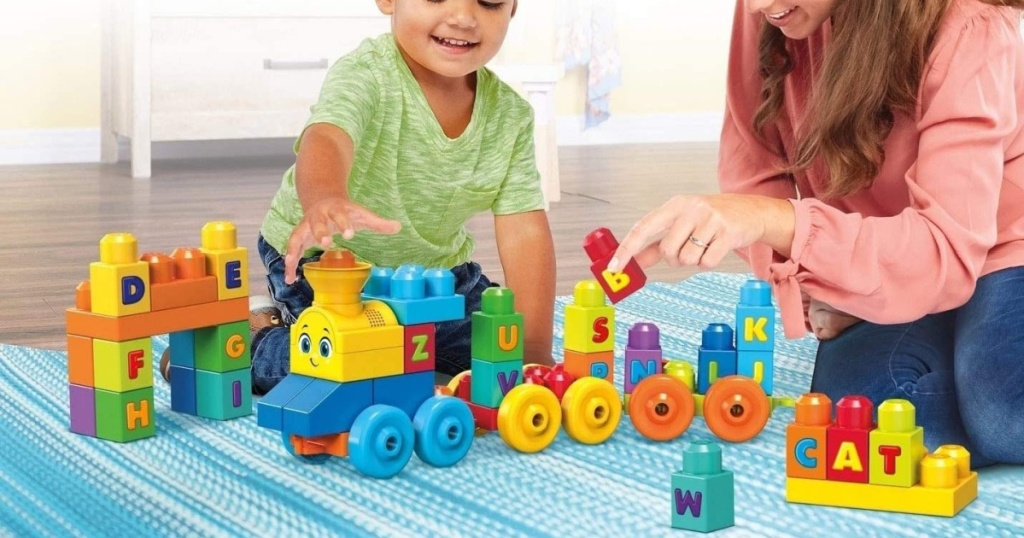 small child and woman sitting on the floor playing with a mega bloks train set