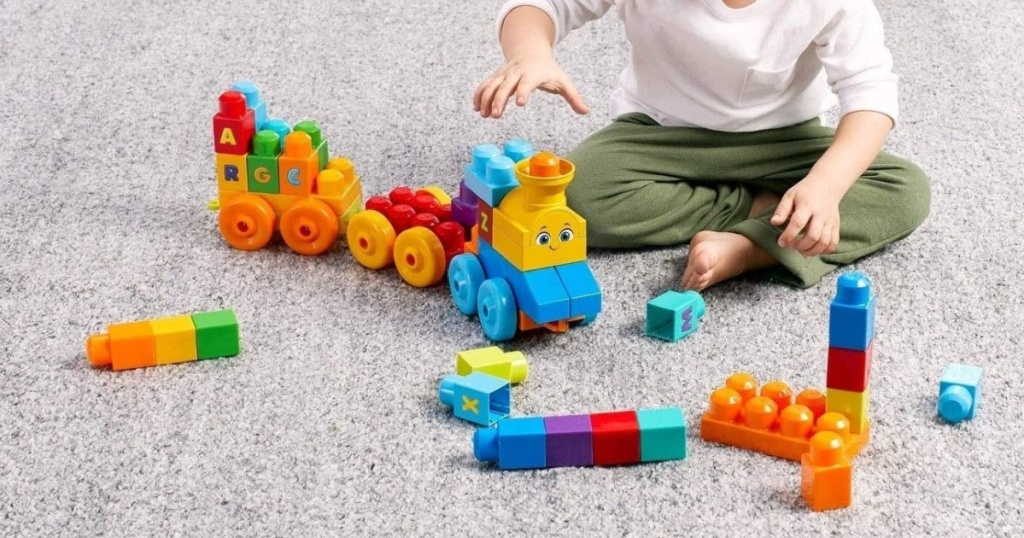 little boy sitting on the floor playing with a mega block train set